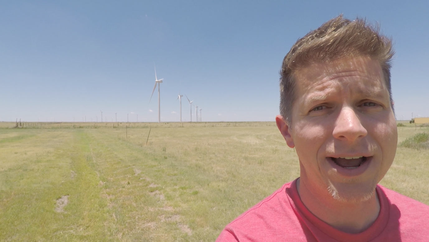 Dennis Cheatham in front of wind turbines on the plains of Texas